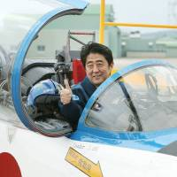 Prime Minister Shinzo Abe poses inside a T-4 training jet during a tour of the Air Self-Defense Force base in Higashimatsushima, Miyagi Prefecture, in May 2013. | AFP-JIJI
