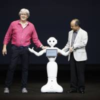SoftBank Corp. Chief Executive Masayoshi Son and Aldebaran Robotics CEO Bruno Maisonnier present the Pepper, a new robot that it says can read human emotions, during a news conference in Urayasu, Chiba Prefecture, on Thursday. | REUTERS