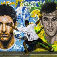 Residents of a favela in Rio de Janeiro play street soccer in front of a mural of Argentine national team lynchpin Lionel Messi (left) and Brazilian star Neymar. The FIFA World Cup kicks off Thursday in Brazil. | AFP-JIJI