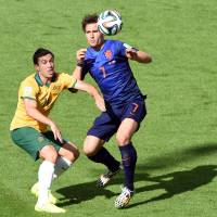 Thrilling match: Australia's Mathew Leckie (left) eyes the ball with the Netherlands' Daryl Janmaat on Wednesday in Porto Alegre, Brazil. The Netherlands won 3-2. | AFP-JIJI