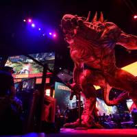 Gaming fans play 'Evolve' for the PlayStation 4 at the annual E3 video game extravaganza in Los Angeles on Tuesday. | AFP-JIJI