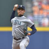 Strikes out seven: Seattle's Hisashi Iwakuma throws a pitch against Atlanta in the first inning on Wednesday. | REUTERS
