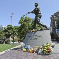 Mr. Padre: Flowers are left at the statue of Tony Gwynn outside Petco Park on Monday. Gwynn, a native of Los Angeles, played his entire 20-year career with the San Diego Padres. | AP