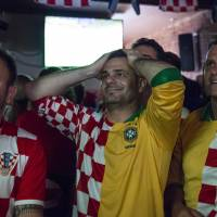 Keeping shirts on: Croatian fans in the Astoria neighborhood of Queens, in New York, wear composite Croatian/Brazilian jerseys while watching the opening soccer match of the World Cup on June 12. | REUTERS