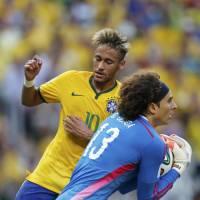Hero of the hour: Mexico goalkeeper Guillermo Ochoa collects the ball ahead of Brazil striker Neymar during their 0-0 draw in World Cup Group A on Tuesday. | REUTERS