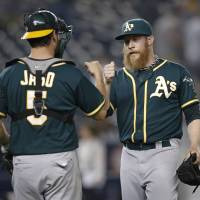 Job well done: Oakland catcher John Jaso (left) congratulates reliever Sean Doolittle after closing out the 10th inning of the Athletics' 5-2 win over the Yankees in New York on Tuesday. | AP