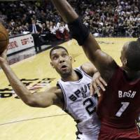Concentration: San Antonio's Tim Duncan puts up a shot around Miami's Chris Bosh in Game 1 on Thursday night. | AP
