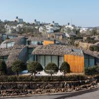 Part of nature: Volcanic rubble is laid across the curved rooftops of villas at Jeju Ball hotel by architect Kengo Kuma on Jeju Island, South Korea. | COURTESY OF KENGO KUMA AND ASSOCIATES