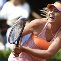 Pushed hard: Maria Sharapova plays a shot from Canada's Eugenie Bouchard in their semifinal match at the French Open on Thursday. Sharapova won 4-6, 7-5, 6-2. | AFP-JIJI