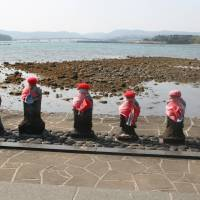 Seven semi-submerged (at high-tide) stone jizō statues. | EDAN CORKILL