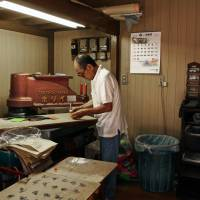 Man and machine: Kazuo Yasukawa die-cuts leather for luxury brands in the small factory where he works. | KIT NAGAMURA