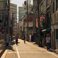 The afternoon sun casts shadows on a narrow alley in Higashi-Ueno. | KIT NAGAMURA