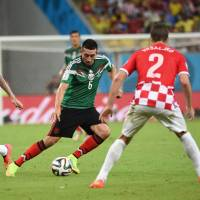 In control: Mexico's Hector Herrera moves the ball between Croatia's Mario Mandzukic (left) and Sime Vrsaljko in Recife, Brazil, on Monday. Mexico won 3-1. | AFP-JIJI