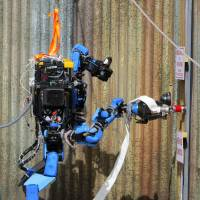 Helping hand: Schaft, a disaster-relief robot, connects a hose to a fire extinguisher.   KYODO