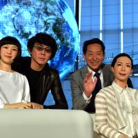 Mamoru Mori (second from right), a former astronaut and the director of the National Museum of Emerging Science and Technology (Miraikan) and Hiroshi Ishiguro (second from left), a professor at Osaka University, pose with humanoid robots Otonaroid (right) and Kodomoroid (left) at the museum on Tuesday. | AFP-JIJI