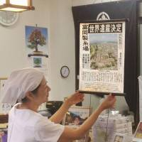 An employee at a shop near the Tomioka Silk Mill in Gunma Prefecture on Sunday displays a special edition of the daily Jomo Shimbun made of silk. | JOMO SHIMBUN/KYODO