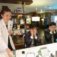 Participants in a grooming workshop for men try a skin lotion at a Tokyo hotel in April. | KYODO