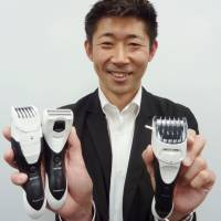 Panasonic employee Katsuhiro Jinnouchi shows off a line of body shavers he has designed for men. | KYODO