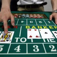 A Japan Casino School employee in Tokyo deals cards on a blackjack table on June 16. | BLOOMBERG