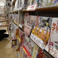 'Ichi Efu' (second from right), a manga about workers at the heavily damaged Fukushima No. 1 nuclear power plant, is seen on a bookshelf as a staffer rearranges comics at a bookstore in Tokyo on June 23. | REUTERS