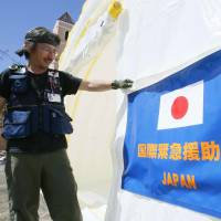 A member of a Japanese medical team sets up an emergency clinic last November on Leyte Island in the Philippines, one of the areas ravaged by Super Typhoon Haiyan, as part of Japan's official development assistance to the country. | KYODO