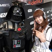 Promoters pose with SMS Audio's 'Star Wars' edition headphones at the Portable Audio Festival in Tokyo's Akihabara district Saturday. | KAZUAKI NAGATA