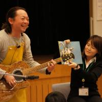 Tetsuya Ando plays guitar during a picture book reading session for fathers and children in Utsunomiya, Tochigi Prefecture, in December 2012. | COURTESY OF TETSUYA ANDO