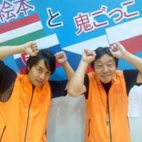 Father and son Yasuo and Takao Hazaki pose June 1 in front of a sign promoting the free outdoor children's game of 'onigokko' as a sport to be enjoyed by all. | TOMOHIRO OSAKI