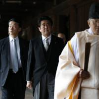 Prime Minister Shinzo Abe is led by a Shinto priest as he visits Yasukuni Shrine in Tokyo on Dec. 26. | REUTERS