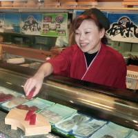 Chie Inamoto, manager and chef of an Isomaru outlet in Atami, Shizuoka Prefecture, serves sushi on April 30. | KYODO