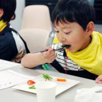 A boy tries vegetables in Shibuya Ward, Tokyo, on May 11 during a course by the Japan Vegetable Sommelier Association. | KYODO