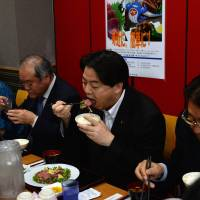 Fisheries Minister Yoshimasa Hayashi eats whale meat during a promotional event in Tokyo on June 9. | AFP-JIJI