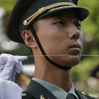 A Chinese People's Liberation Army soldier uses a string to ensure that soldiers, making up an honor guard, stand in a straight line before a ceremony in Beijing on June 12. | REUTERS