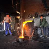Chinese laborers pour molten iron at a foundry in Xiangfan, Hubei province, in this file photo. | REUTERS