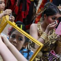 Dancers have their makeup done backstage before a military-organized show at the Victory Monument in Bangkok on Wednesday. | REUTERS