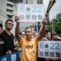 Pro-democracy demonstrators in Hong Kong hold up placards calling on residents to cast ballots for a June 22 referendum, outside Beijing's local representative office on Wednesday. | AFP-JIJI