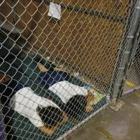 Two female detainees sleep in a holding cell at the U.S. Customs and Border Protection Nogales Placement Center in Arizona on Wednesday. | AP