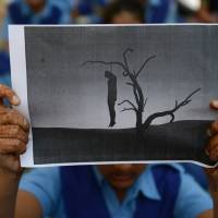 A schoolgirl holds a placard with an image of a hanged man during a rally in Ahmedabad following the death of a gang-rape victim in New Delhi in December 2012. | AFP-JIJI