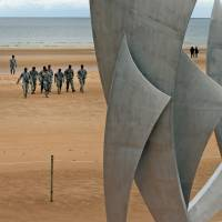Members of the U.S. 82nd Airborne Division from Fort Bragg, North Carolina, collect sand as a souvenir from Omaha Beach at St. Laurent sur Mer, northern France, on Wednesday, ahead of D-Day commemorations Friday. The monument in the foreground is titled 'The Brave.' | AP