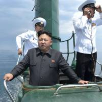 North Korean leader Kim Jong Un surveys the scene from the conning tower of an aging Romeo-class submarine during his inspection of a Korean People's Army naval unit in a photo released by the North's official news agency Monday. | REUTERS