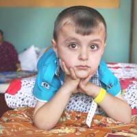 A displaced Iraqi Christian boy who fled from the village of Hamdania sits at a temporary shelter for families in Ainkawa, a suburb of Irbil with a majority  Christian population, on Friday. | AP
