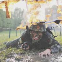 A Chinese paramilitary member crawls under fire obstacles during a drill at a base in Chaohu, Anhui province, on May 5. | REUTERS