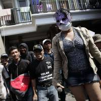 A masked sex worker protests plans to close the 'Dolly' red-light district in Surabaya, Indonesia, on June 5. | AFP-JIJI