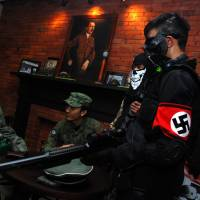 Customers wearing World War II-era military uniforms, one bearing the Nazi swastika, relax in the SoldatenKaffee in Bandung, Indonesian, on Saturday. The cafe, which sparked international outrage and forced its closure, reopened with a large painting of Adolf Hitler still adorning a wall. | AFP-JIJI
