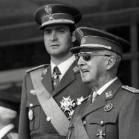 Prince Juan Carlos (left) and Spanish dictator Gen. Francisco Franco attend a parade in Madrid in June 1971. | AFP-JIJI