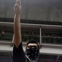 Borrowed from Hollywood, this three-fingered salute is increasingly being used by anti-coup protesters in Bangkok. While opinions differ as to its exact meaning, the Thai military has threatened to arrest those who persist in making use of the sign. | AP