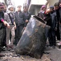 Syrians inspect an unexploded barrel bomb packed with explosives in January after a regime helicopter dropped it on a street in the city of Aleppo. | AP