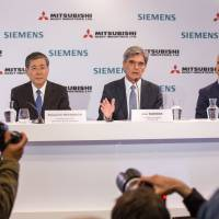 Joe Kaeser, CEO of Siemens AG (center), Shunichi Miyanaga, CEO of Mitsubishi Heavy Industries Ltd. (left) and Frederick Jeske-Schonhoven, secretary-general of Siemens AG France, announce a joint bid for Alstom SA, in Paris on June 17. | BLOOMBERG