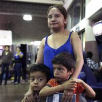 A Guatemalan and her sons — part of about 400 mostly Central American women and children caught crossing from Mexico into southern Texas — wait at the Greyhound bus terminal in Phoenix on May 29. | AP