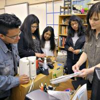 Teacher Amanda Filloy Sharp (right) checks on potluck items with her students (from left) Diego Munoz, Stephanie Vidrio, Thania Lopez and Cynthia Cruz, at the end of class in Corvallis, Oregon, on May 28. | AP